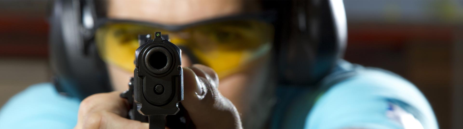 Woman at shooting range behind a gun with yellow goggles and headphones on.