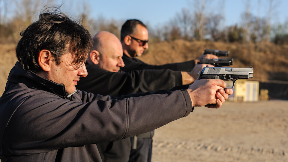 3 men shooting guns at a shooting range and addressing firing line mobility.